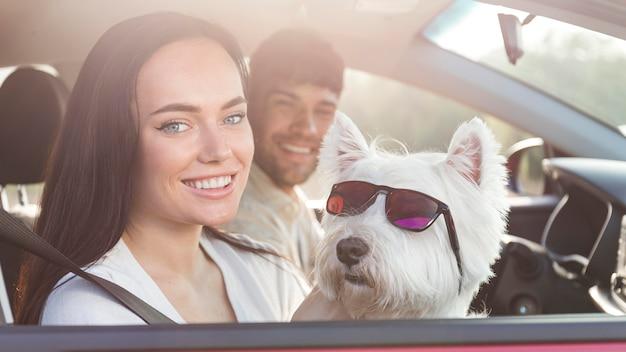 Casal próximo segurando cachorro com óculos de sol