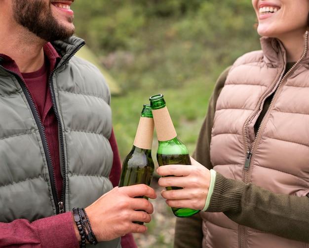 Casal próximo tomando um drinque na natureza