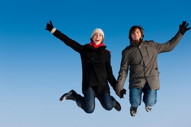 Casal pulando em um dia de inverno