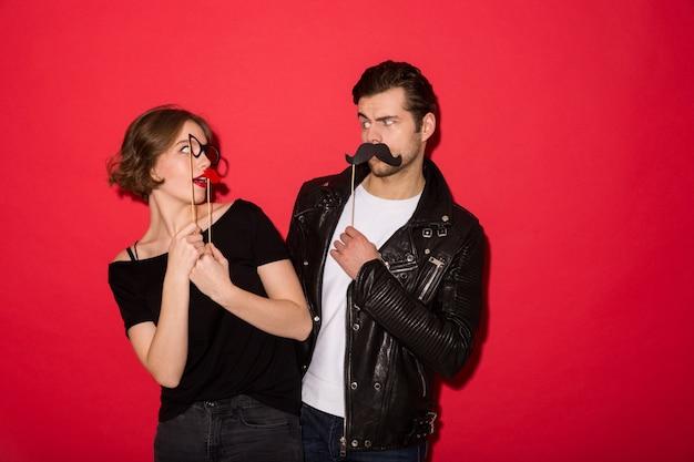 Casal punk brincalhão posando com bigode falso, lábios e óculos