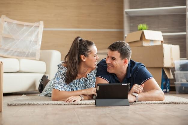 Casal que acabou de se mudar para a nova casa está comprando móveis online em um tablet pc