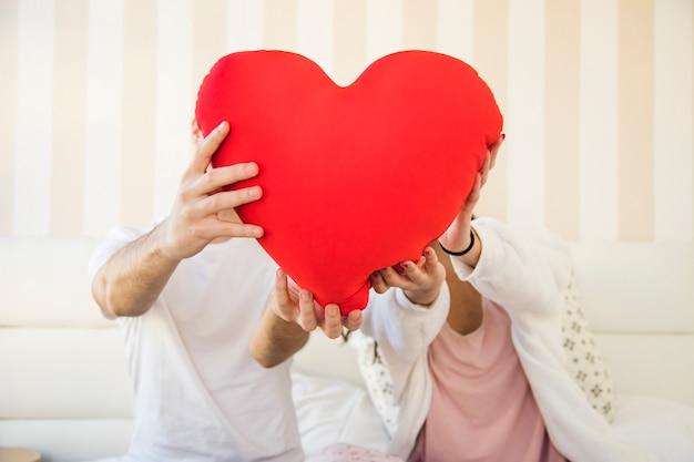 Casal que mostra a almofada do coração para a câmera