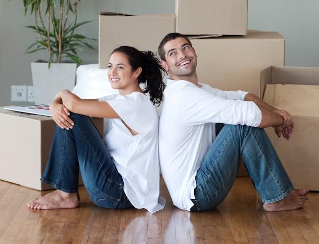 Casal radiante com caixas de desembalagem movendo-se para uma nova casa