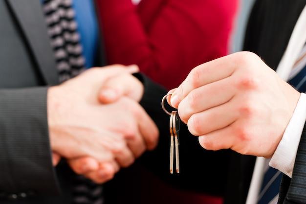 Casal recebendo chaves do corretor de imóveis