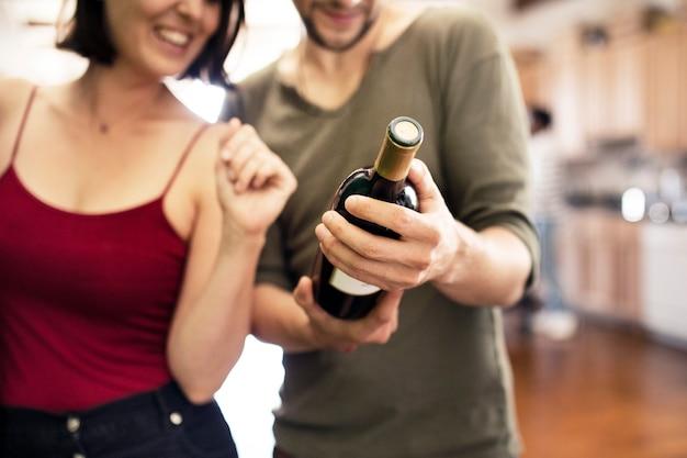 Casal recebendo uma garrafa de vinho tinto Foto Premium