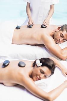 Casal recebendo uma massagem com pedras quentes à beira da piscina