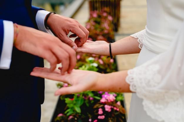 Casal recém-casado acariciando as palmas das mãos.