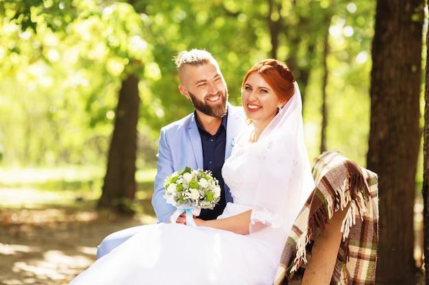 Casal recém casado amoroso hipster em vestido de noiva e terno no parque