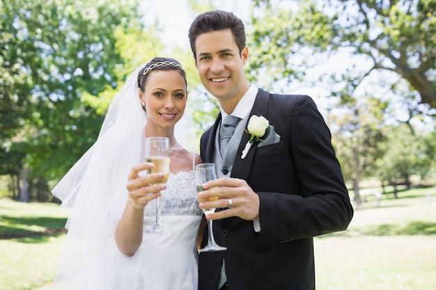 Casal recém-casado brindando champanhe no parque