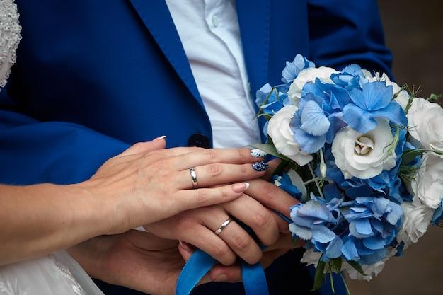 Casal recém-casado de mãos dadas e exibindo os anéis de casamento, close-up.