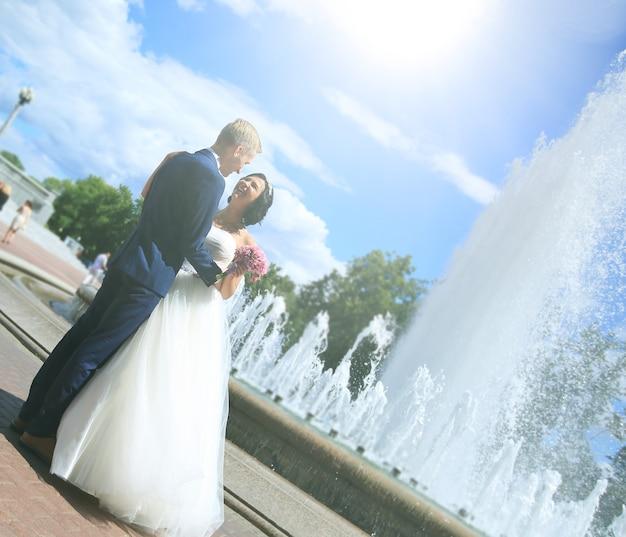 Casal recém-casado em pé perto de uma fonte