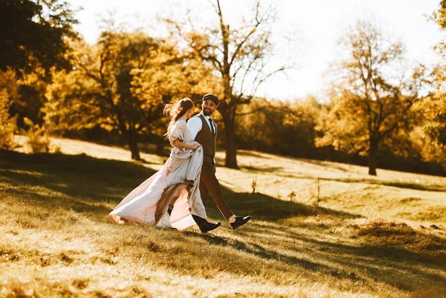 Casal recém-casado feliz caminhando na floresta durante o pôr do sol