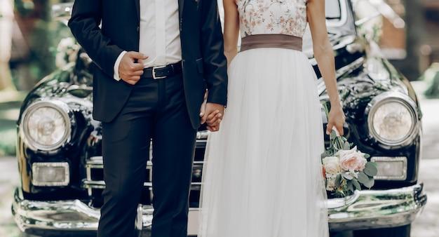 Casal recém-casado na frente de um carro clássico preto