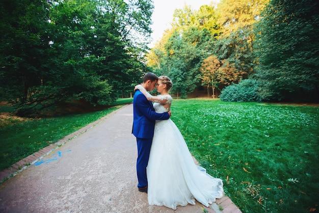Casal recém-casado no parque recém casados caminhe no parque e abraça