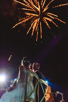 Casal recém-casado, olhando para os fogos de artifício do céu.