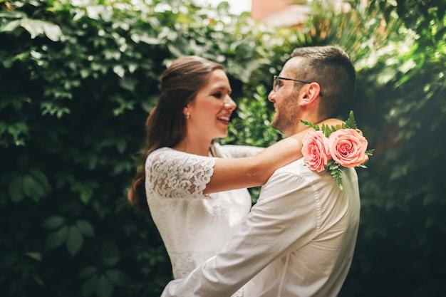 Casal recém-casado, olhando um ao outro, abraçando a dança e sorrindo no dia do casamento. união e o conceito de amor.