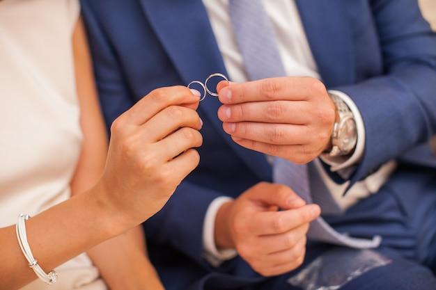 Casal recém-casado segurando em seus dedos duas alianças de casamento. noivo e noiva mostrando par de anéis de noiva.