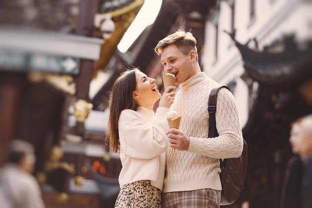 Casal recém-casado tomando sorvete de um cone em uma rua em xangai, perto de yuyuan china.