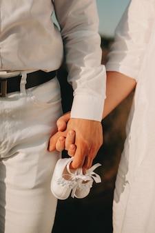 Casal recém-casado, vestido com roupas brancas, anda de mãos dadas enquanto segura um par de sapatos de bebê