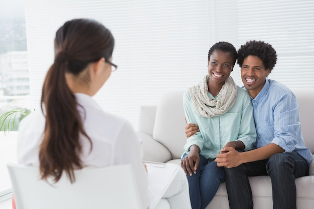 Casal reconciliado sorrindo para o seu terapeuta