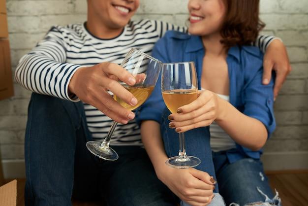 Casal recortado, sentado no chão e tilintar de copos de vinho