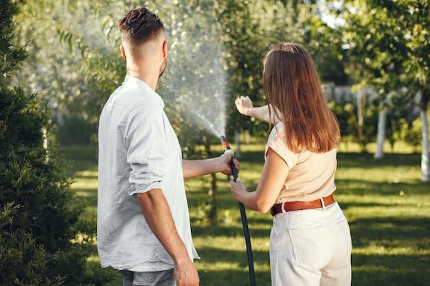 Casal regando as plantas em seu jardim. homem de camisa azul. família trabalha em um quintal.