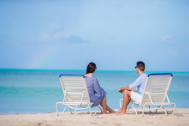 Casal relaxa em uma praia tropical nas maldivas