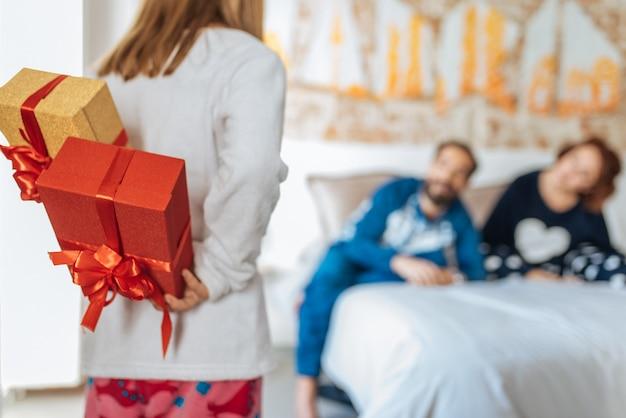 Casal relaxado em casa na cama com a filha fazendo uma surpresa com presentes