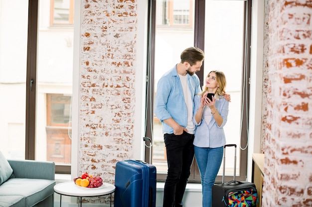 Casal relaxado ou amigos, homem e mulher, usando um telefone celular juntos em pé no quarto moderno no hotel depois de chegar
