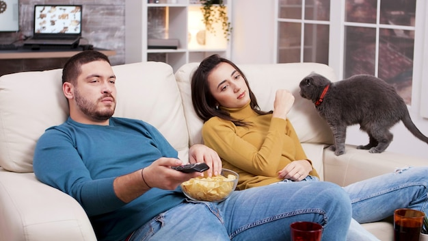 Casal relaxando assistindo a um filme na tv e brincando com o gato. homem usando o controle remoto da tv e comendo batatinhas.