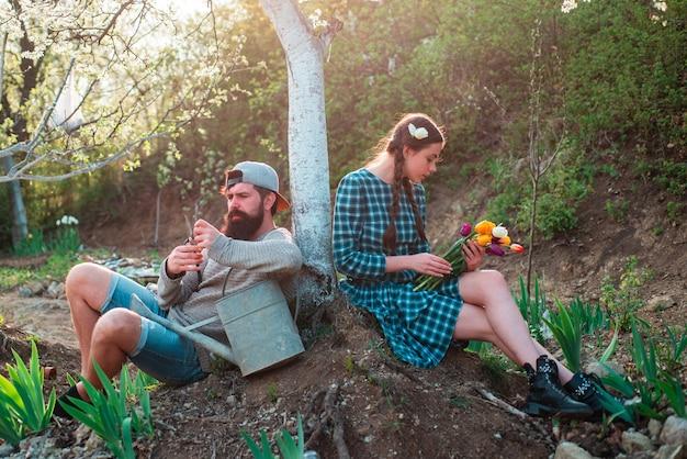 Casal relaxando depois de um trabalho árduo. amigos planta e cultiva plantas. amigos que trabalham no jardim.