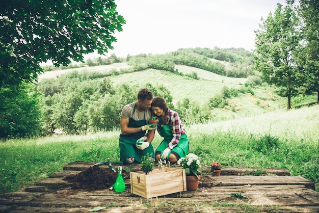 Casal relaxando e plantando algumas flores no quintal da casa de campo