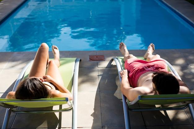 Casal relaxando em uma espreguiçadeira à beira da piscina em um dia ensolarado