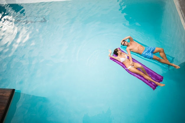 Casal relaxando na balsa inflável na piscina