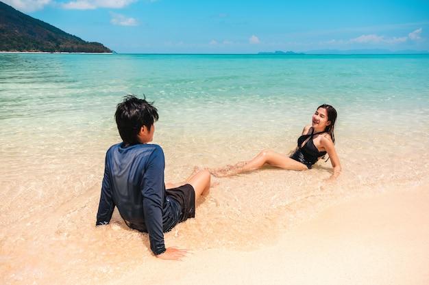 Casal relaxando na praia de férias de verão