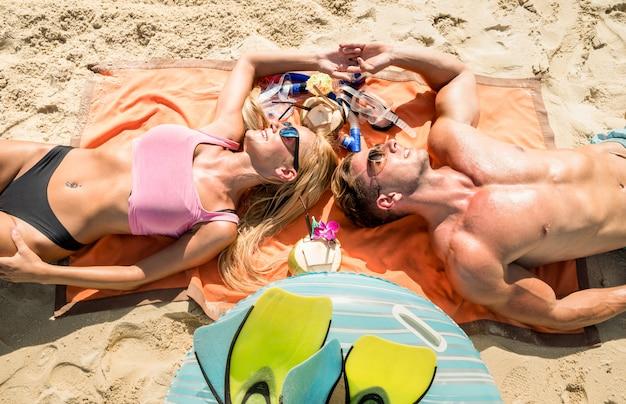 Casal relaxando na praia tropical - conceito de férias viagem de verão