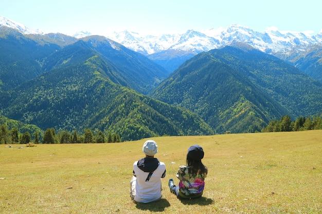 Casal relaxando no prado de highland, admirando a vista da montanha do cáucaso, mestia, geórgia