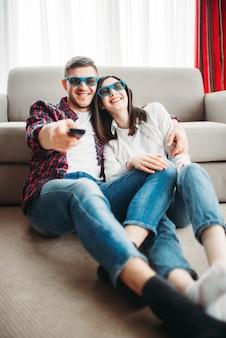 Casal rindo com óculos 3d sentado no chão, encostado no sofá, assistindo tv em casa