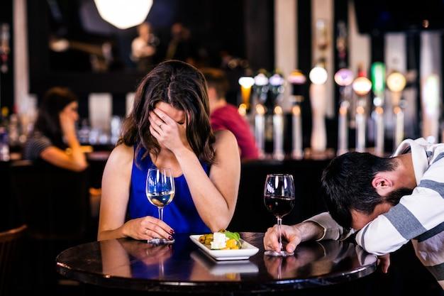 Casal rindo e tomando uma bebida em um bar
