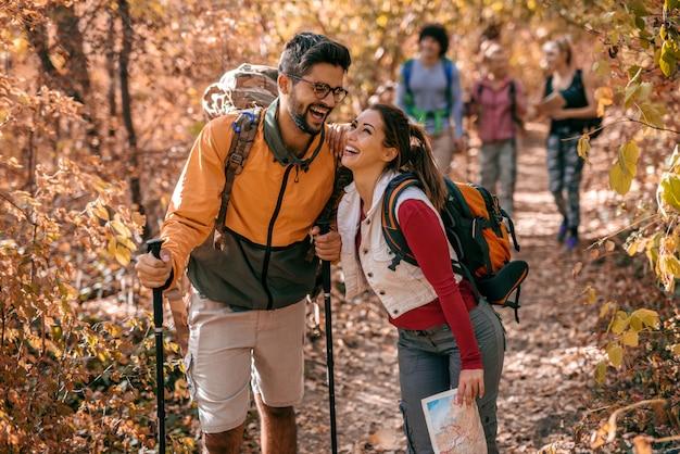 Casal rindo enquanto caminhava na floresta.