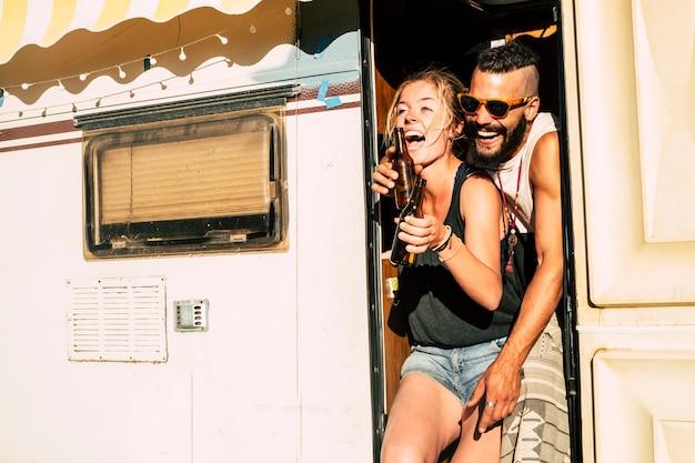 Casal rindo muito e se divertindo juntos em um relacionamento e amizade na porta de uma velha caravana de campista retrô para férias alternativas ao ar livre.