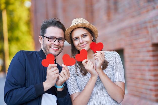 Casal romântico adulto segurando corações enquanto caminha pela cidade