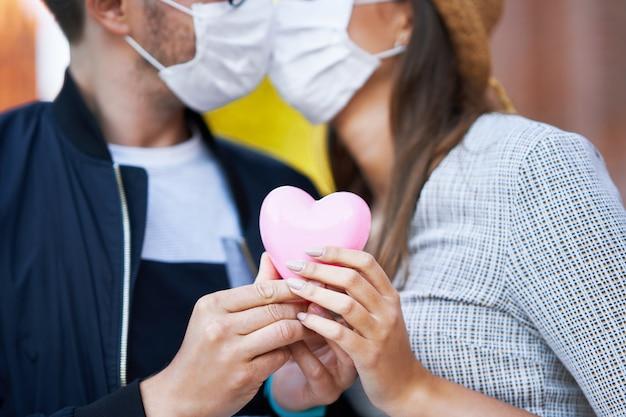 Casal romântico adulto usando máscaras em uma caminhada pela cidade
