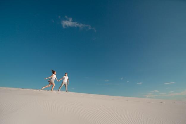 Casal romântico apaixonado correndo na areia branca no deserto