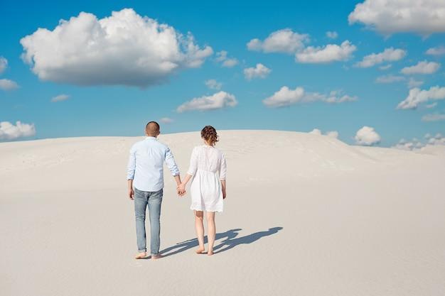 Casal romântico apaixonado na areia branca no deserto.