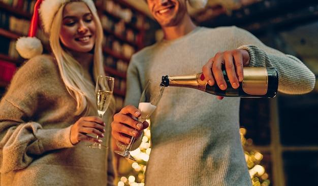 Casal romântico apaixonado, sentindo felicidade por seu romance passar o natal ou ano novo juntos. um homem derrama champanhe em taças.