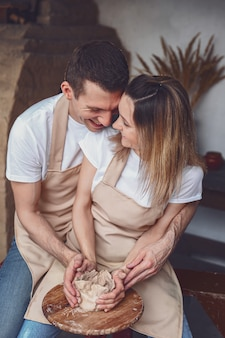 Casal romântico apaixonado trabalhando juntos na roda de oleiro e esculpir a panela de barro