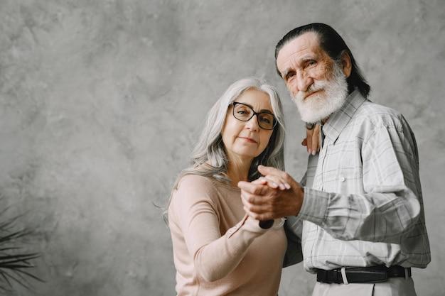 Casal romântico aposentado velho ativo alegre dançando na sala de estar.