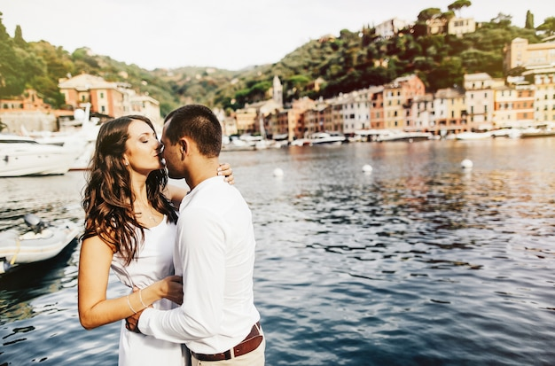 Casal romântico caminhando na praia ao pôr do sol