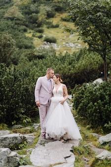 Casal romântico casamento apaixonado pé do lago sea eye na polônia. montanhas tatra.